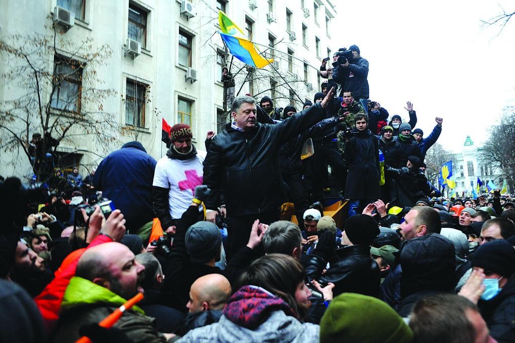 После избиения студентов, в центр Киева выплеснулось более миллиона разгневанных горожан. Нам тогда казалось: это должно подействовать на власть отрезвляюще. Но власть уже подготовила продолжение кровавого плана: бойня на Банковой готовилась заранее. На фото – внефракционный депутат Петр По- рошенко пытается сдержать движение грейдера, атакующего позиции силови- ков перед Администрацией Президента. Уже через полтора часа Банковая по- двергнется жесткой зачистке – беркут будет жестоко избивать и захватывать в заложники всех, кто подвернется под руку.