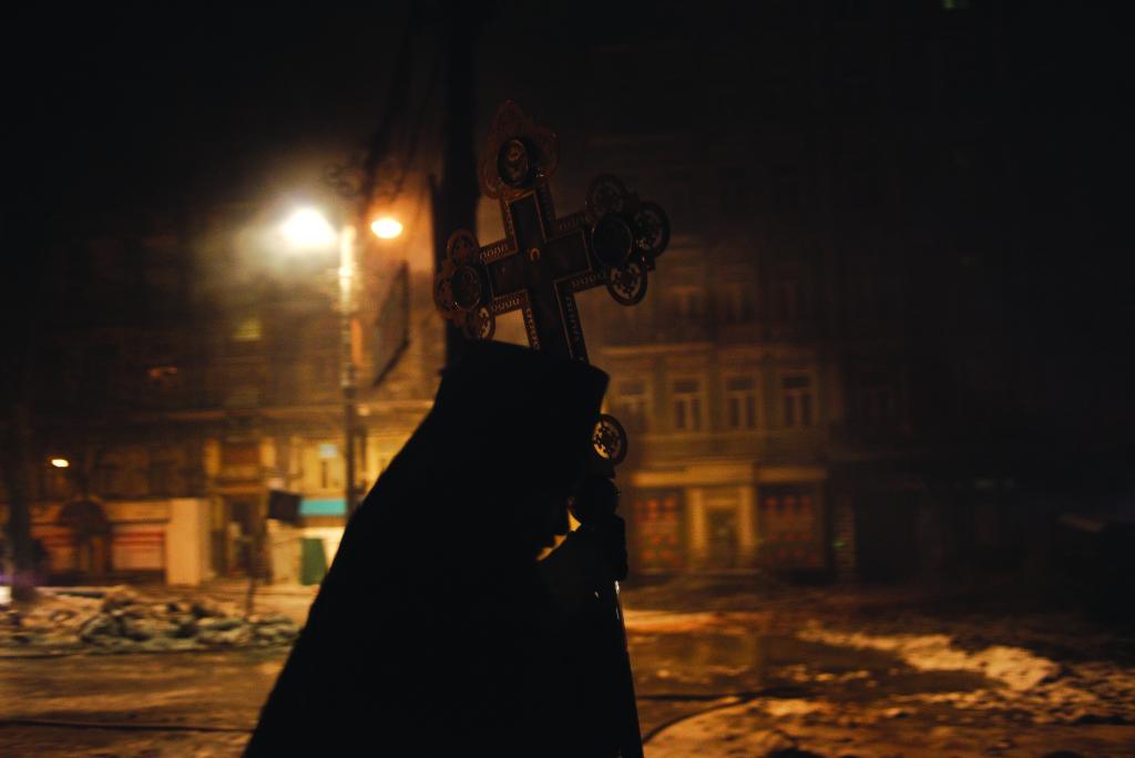 Священник с крестом. На протяжении всего времени стояния Майдана, священники раз- ных христианских церквей сыграли огром- ную роль, постоянно присутствуя на барри- кадах, вознося молитвы к Богу и призывая стороны к миру.